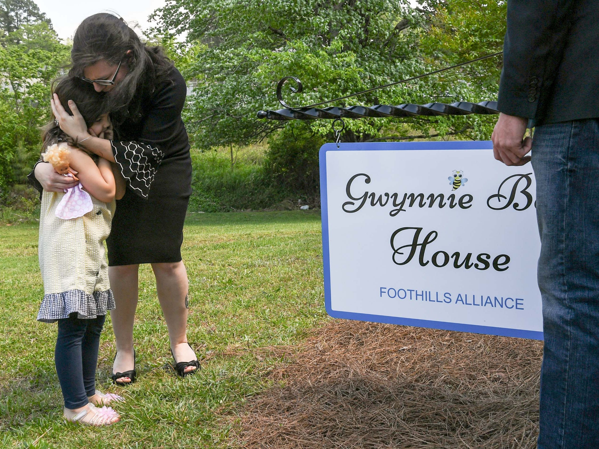 "Ravyn Hammond hugs her daughter Gracie Hess after a sign was unveiled during an office dedication of the Foothills Alliance Oconee County Gwynnie Bee House in Walhalla Friday. Foothills Alliance, who with partners provides education, advocacy, and treatment services to prevent sexual assault trauma and child abuse services in Anderson and Oconee Counties, branched out from their Anderson office with an office in Walhalla last August. Hammond lost her daughter Gwynne Ann-Marie Hess, ""Gwynnie Bee"", in 2017 from child abuse, and the office was renamed after her Friday in the presence of family, law enforcement, Sen. Thomas Alexander, Oconee County Sheriff Michael Crenshaw, and Tenth Circuit Solicitor David Wagner."