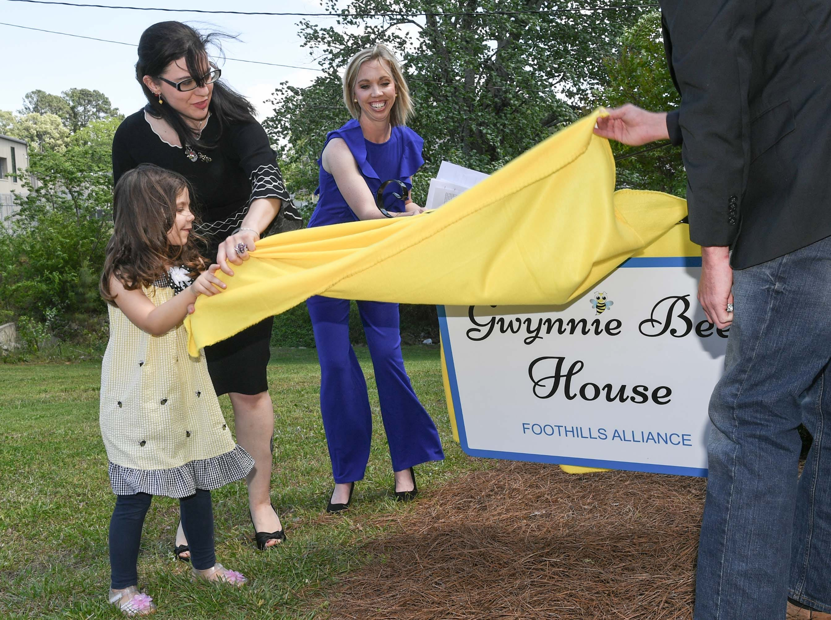 "Gracie Hess, left, pulls a cloth off a sign with her mother Ravyn Hammond, middle, and Sandra Campbell, right, Foothills Alliance counselor, during an office dedication of the Foothills Alliance Oconee County Gwynnie Bee House in Walhalla Friday. Foothills Alliance, who with partners provides education, advocacy, and treatment services to prevent sexual assault trauma and child abuse services in Anderson and Oconee Counties, branched out from their Anderson office with an office in Walhalla last August. Hammond lost her daughter Gwynne Ann-Marie Hess, ""Gwynnie Bee"", in 2017 from child abuse, and the office was renamed after her Friday in the presence of family, law enforcement, Sen. Thomas Alexander, Oconee County Sheriff Michael Crenshaw, and Tenth Circuit Solicitor David Wagner."