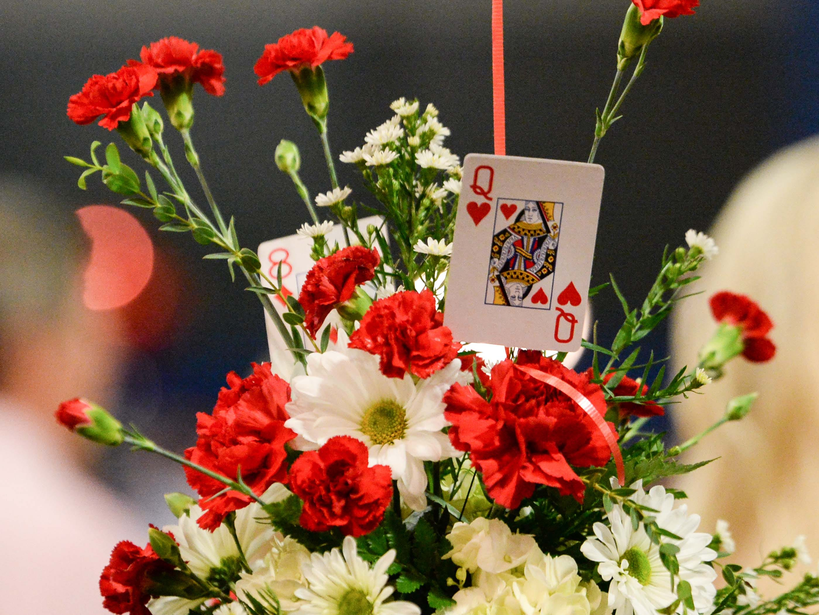 "A table display of carnations and playing cards during the 13th Dancing For Our Heroes event with the theme ""Welcome to Las Vegas"" at the Civic Center of Anderson Thursday."