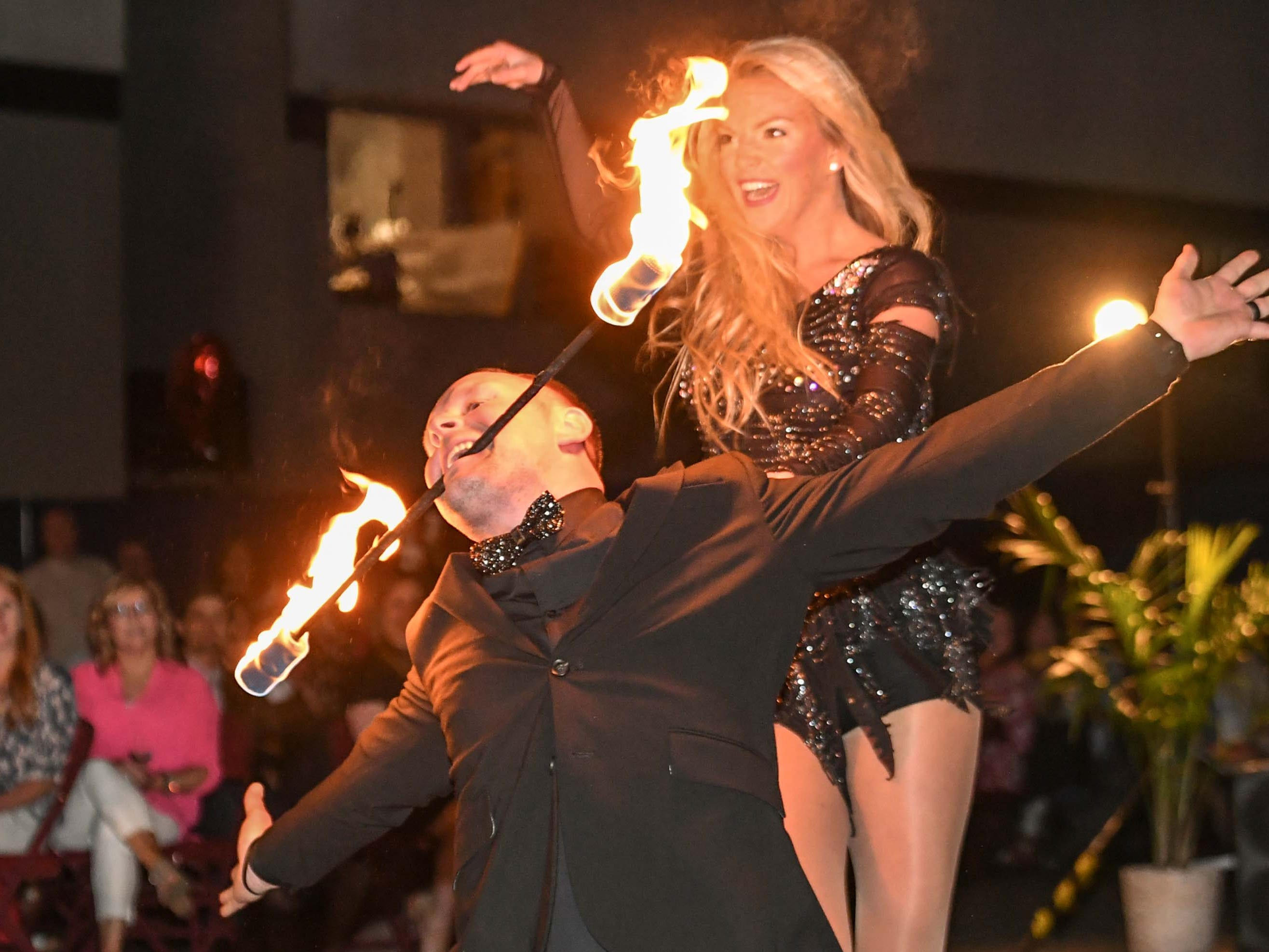 "Jeremy Caldwell, left, holds a baton with flames with his teeth near Ansley Cartee, dancing to a medley of songs by Britney Spears during the 13th Dancing For Our Heroes event with the theme ""Welcome to Las Vegas"" at the Civic Center of Anderson Thursday. The dance couple raised $35,848 for AnMed Health Foundation. The ten dance couples raised money for different charities, dancing to acts who have residencies in Las Vegas."