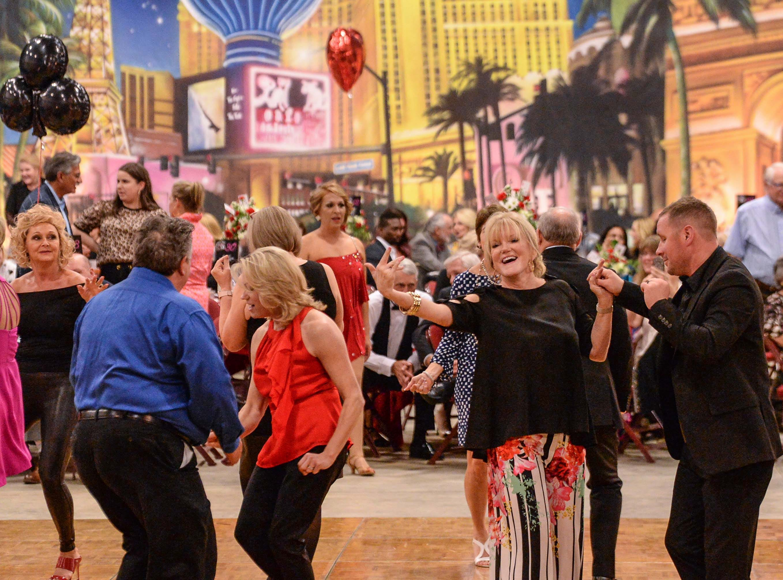 "Dancers and supporters join on the dance floor after competition during the 13th Dancing For Our Heroes event with the theme ""Welcome to Las Vegas"" at the Civic Center of Anderson Thursday."