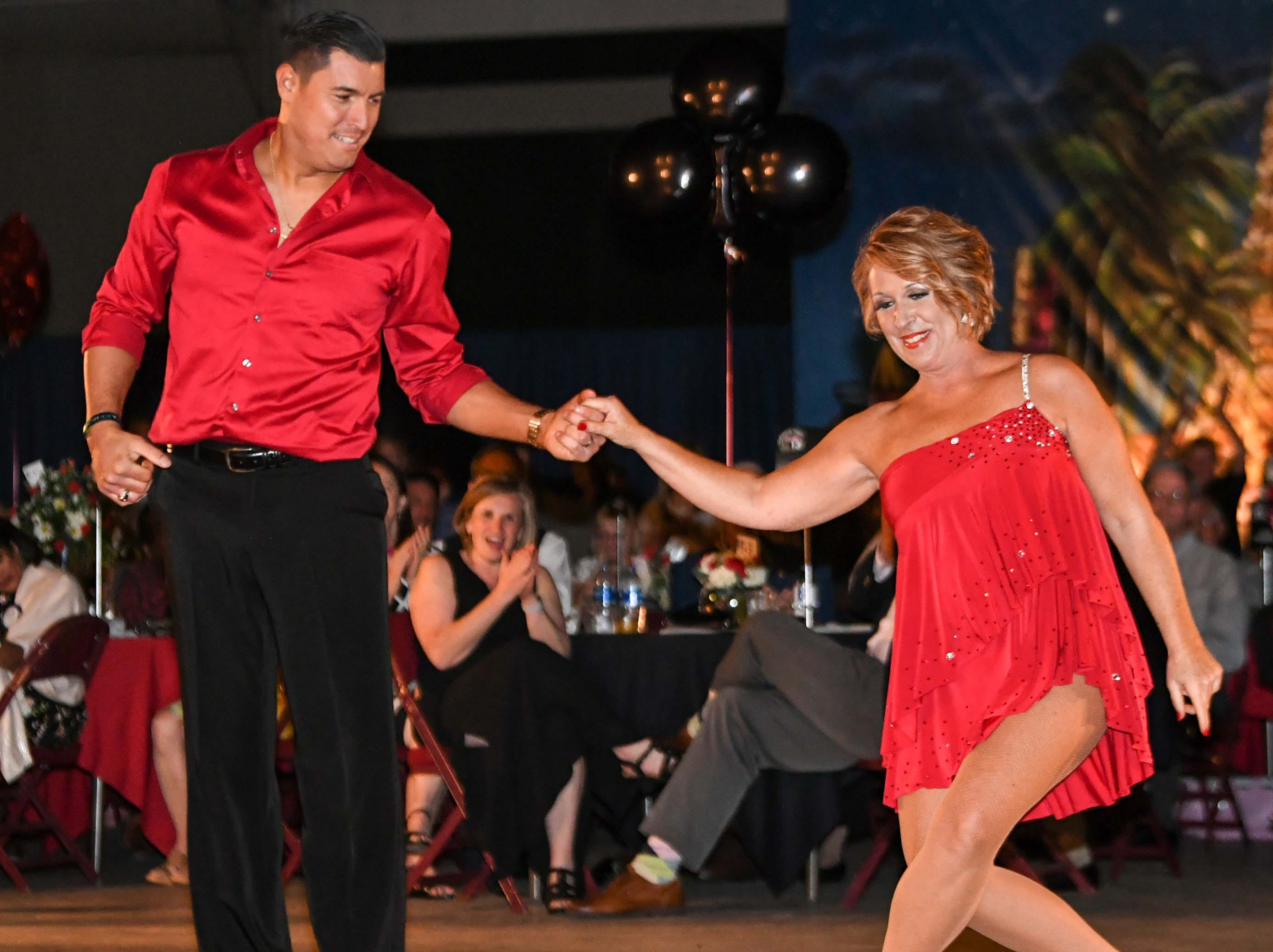 "Carla Parker, right, and Luis Martinez dance to music by artist Pitbull during the 13th Dancing For Our Heroes event with the theme ""Welcome to Las Vegas"" at the Civic Center of Anderson Thursday. The dance couple were raising money for Cancer Association of Anderson. The ten dance couples raised money for different charities, dancing to acts who have residencies in Las Vegas."