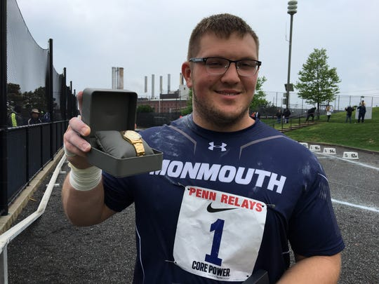 Monmouth's Corey Murphy holds up his gold watch for winning the shot put at the Penn Relays.