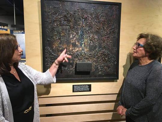 Dale Daniels (left) and Claire Boren (right) look at Boren's painting of the hole in the barn where she hid from the Nazis.