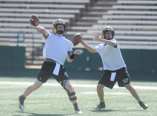 Abilene High quarterbacks Eric Abbe, left, and Abel Ramirez get ready to throw passes during the Eagles' first spring practice.