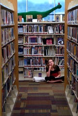 Abby Jensen, 13, pauses to look at a poster while reading a Supergirl graphic novel Thursday at the Abilene Public Library Mockingbird Lane branch. Lib-con continues at the library's Main Branch downtown Saturday.