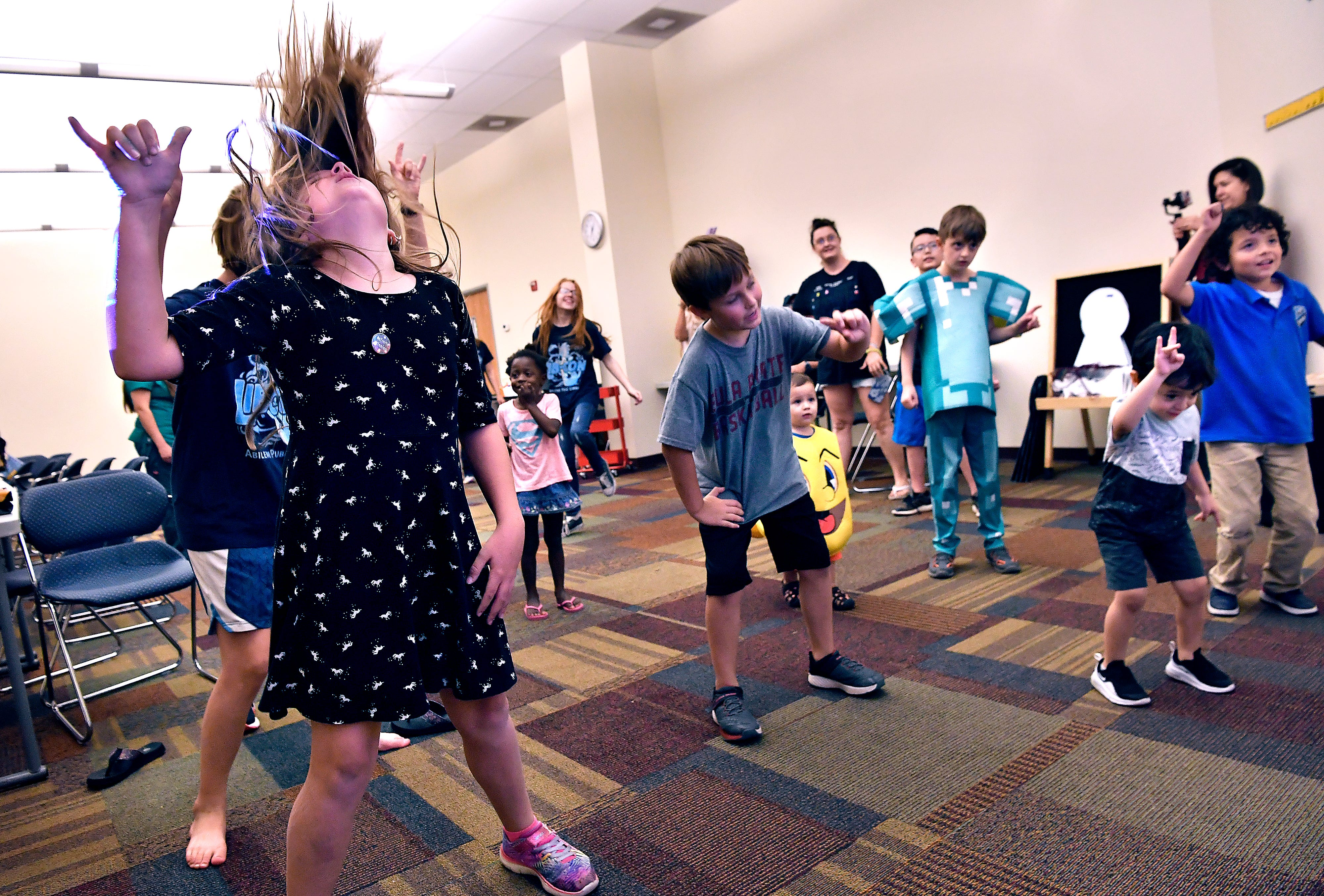 Children head-bang to a video dance game Thursday during the Fortnight Party & Dance Marathon at Lib-con in the Abilene Public Library's Mockingbird Lane branch. Different dances played out by onscreen characters would switch-out every several seconds, with the kids doing their best to keep up.