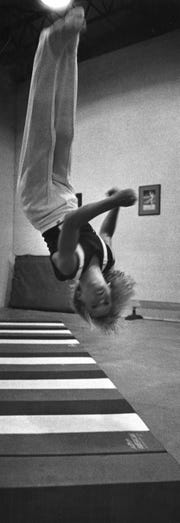 Mark Oates, 12, does a back flip full twist at the YMCA gym in 1975.