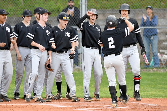 North Buncombe celebrates Heath Fox's home run as he crosses the plate during their game at Asheville High School on April 26, 2019. The Cougars defeated the Blackhawks 4-2.