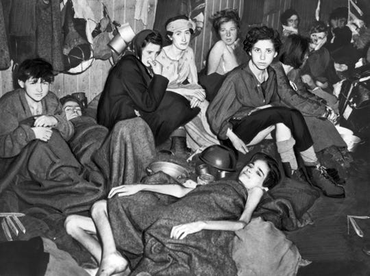 A picture taken in April 1945 in Nazi Bergen-Belsen concentration camp, after its liberation by the British troops, shows female deportees suffering from typhus, starvation and dysentery waiting in a barrack for their evacuation by the Allied authorities.