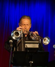 Jeff Stockham plays two trumpets at a jazz session at the Schorr Family Firehouse Stage.