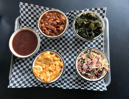 Clockwise from left: Barbecue sauce, baked beans, collard greens, coleslaw, and macaroni and cheese are all sides served up at the BelAir BBQ Diner in Endicott.