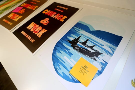 Previous editions of Heavy Jeens posters on display at Pier Six Press.
