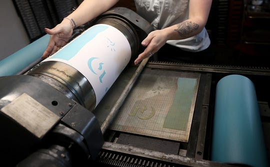Karen Sawyer, of Pier Six Press, prints posters for her Heavy Jeens project on the press in the basement of her home in Bremerton on Thursday, April 25, 2019. Every First Friday Sawyer creates an edition of handmade posters and distributes them around town - those who find them get to take them home.