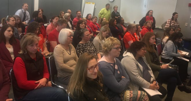 Teachers and other staff in North Kitsap School District listen as the board considers proposed cuts of up to $3 million, including 20 teaching positions, on Thursday.