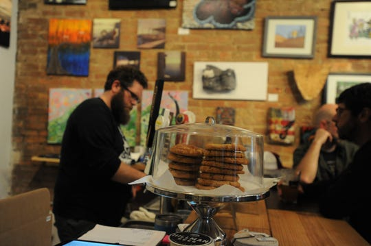 Randy Giles serves customers during Featured Artist Pint Night at his business BAD Craft, which features local craft beer, art and desserts.
