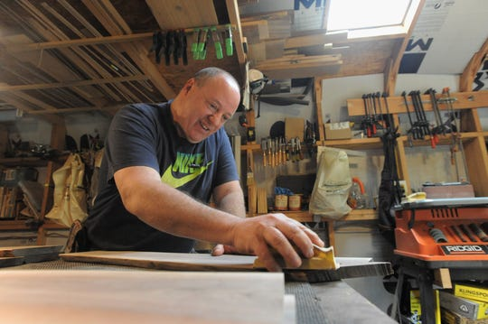 Rick Pocock, owner of Full Dimension Woodwork, sands a piece of wood as he prepares for the upcoming season of the Black Mountain Tailgate Market.