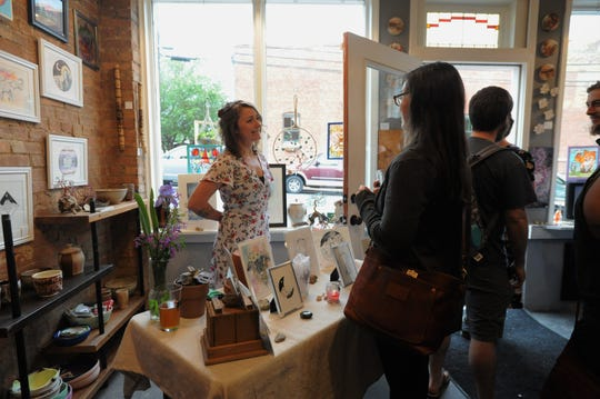 Melissa Autumn Raines greets people at BAD Craft on Cherry Street on April 25, when she was the featured artist for the Black Mountain business's monthly Featured Artist Pint Night.