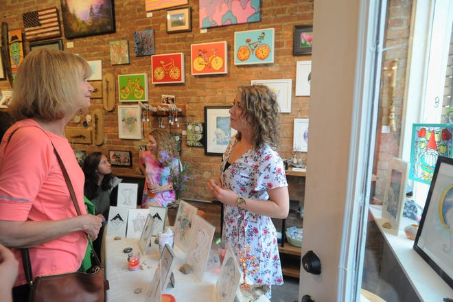 Melissa Autumn Raines, right, greets customers at BAD Craft on April 25 during Featured Artist Pint Night at the Black Mountain business.