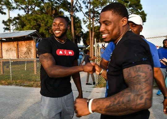 Jamel Dean (left) and Chauncey Gardner-Johnson greet each other at a 2019 NFL Draft party prior to being selected.
