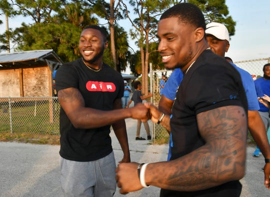Jamel Dean (left) and Chauncey Gardner-Johnson greet each other at Thursday's NFL Draft party at the McKnight Family Sports Complex in Rockledge.