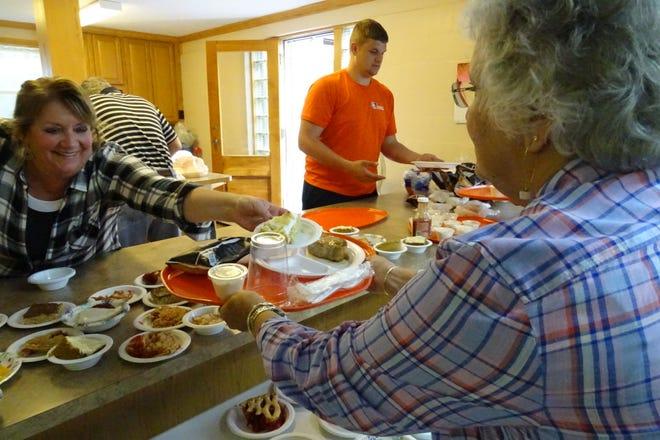 Sarah Shifley, left, hands Bonnie Allen a slice of butterscotch pie during the annual pork chop dinner at Mount Zion United Methodist Church on Thursday.