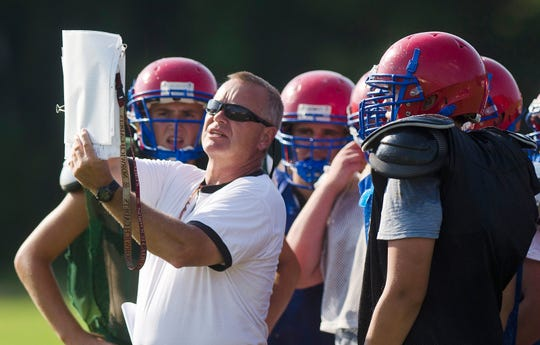 Hartford High School football coach Mike Stone (second from left) describes a play to his team during a preseason practice in 2013.