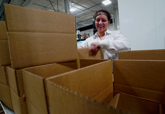 Teilya Brunet boxes up supplements at Food Science in Williston, a job she landed through Working Fields which specializes in helping people in recovery find employment as well as offering support and oversight.