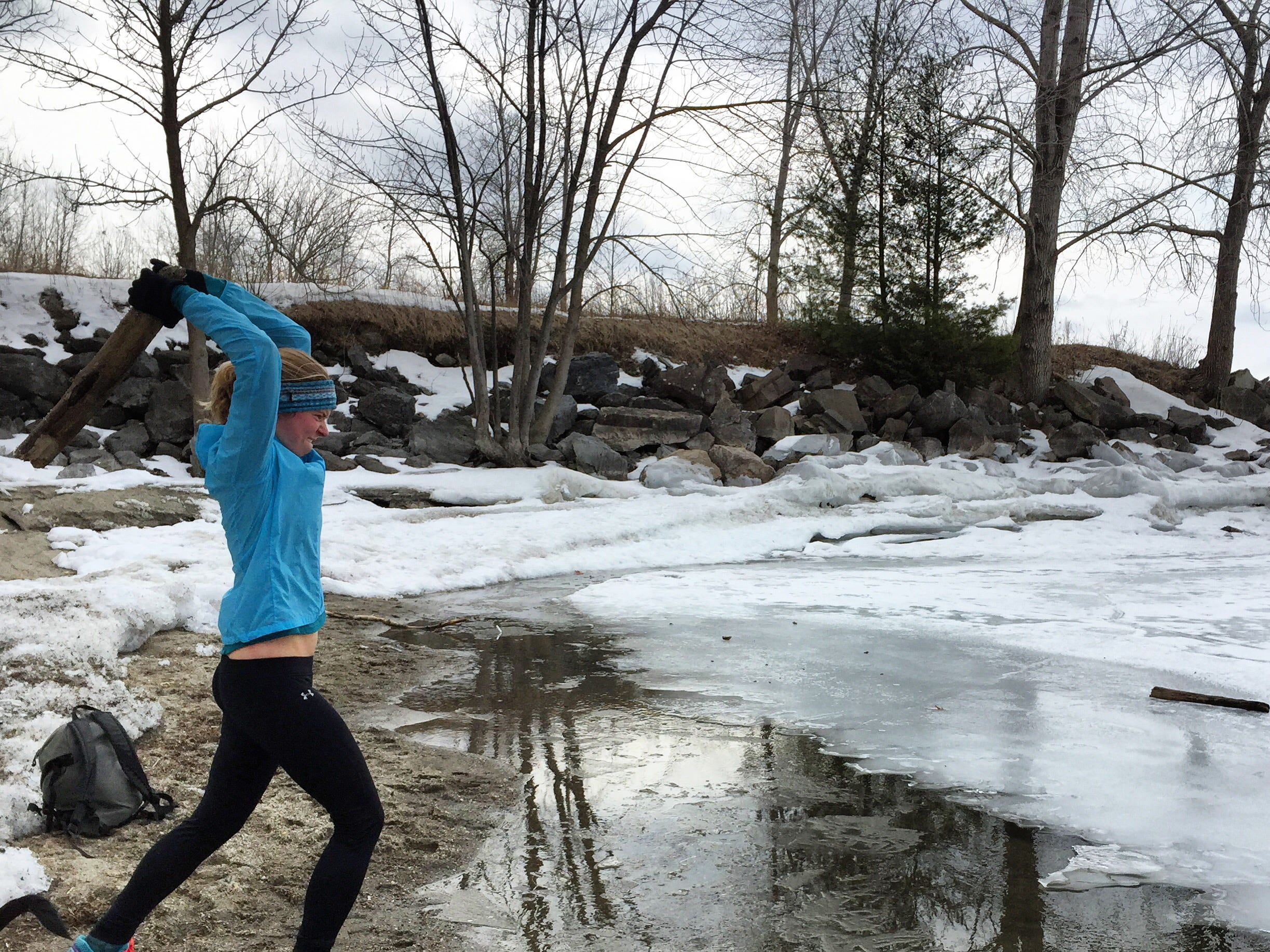 """Monika Derrien, a year-round """"dipper"""" in Lake Champlain, hurls a piece of wood in order to break up ice on March 21, 2015."""