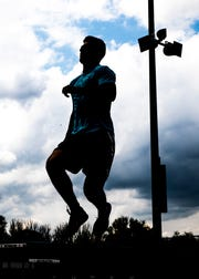 Lane Ruby jumps in the air as he does multiple warm up exercises before he and other team mates practice the 4x100 meter dash on Tuesday, April 23, 2019, at Southeastern High School.