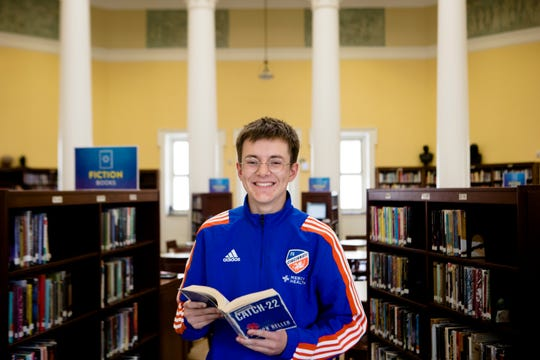 "Senior Ray Conroy, 18, stands inside the library at Walnut Hills High School holding his favorite book, ""Catch 22,"" on Friday, April 26, 2019. Conroy scored a 36 on the ACT."