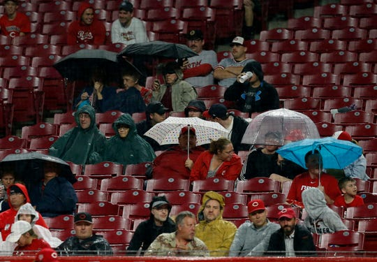 Fans pop umbrellas as rain falls in the seventh inning of the MLB National League game between the Cincinnati Reds and the Atlanta Braves at Great American Ball Park in downtown Cincinnati on Thursday, April 25, 2019.