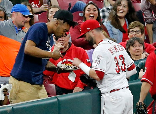 Cincinnati Reds left fielder Jesse Winker (33) pretends to grab a snack from a fan after catching a pop up in foul territory off the bat of Atlanta Braves right fielder Nick Markakis (22) in the sixth inning of the MLB National League game between the Cincinnati Reds and the Atlanta Braves at Great American Ball Park in downtown Cincinnati on Thursday, April 25, 2019. The Reds carried a 3-0 lead as the game entered a rain delay in the seventh inning.