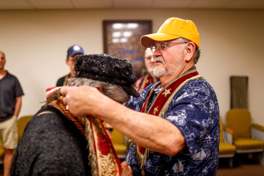 Bobby Haskins places a sash around the neck of another member at Odd Fellows Lodge in Clarksville, Tenn., on Tuesday, April 23, 2019.