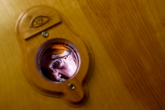 """Bobby Haskins peers through a peep hole in the door leading to the meeting room at Odd Fellows Lodge in Clarksville, Tenn., on Tuesday, April 23, 2019. Traditionally, only a member of the lodge may enter and sit in on meetings, and when one would approach and rap on the door, the member inside would open the peep hole and ask, """"Who comes here?"""""""