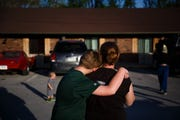 TJ Schmitt, 10 hugs his mother Jess Schmitt in the parking lot of Hotel Arthur where their family of six has been living since their home flooded earlier this month on Wednesday, April 24, 2019, in Glenwood.