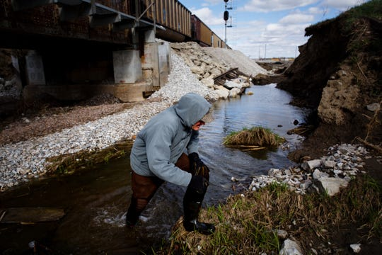 """Pacific Junction Mayor Andy Young steps through water in front of one of the levee breeches that bordered his town on Friday, April 12, 2019. The levee broke on both sides of the railroad adding to the flooding in town, but also raising concerns about more flooding since that creek is where Pacific Junction is pumping out water too. Young believes """"PJ"""" as residents call it, would have flooded even if the levee's didn't break but """"it certainly didn't help,"""" he added."""