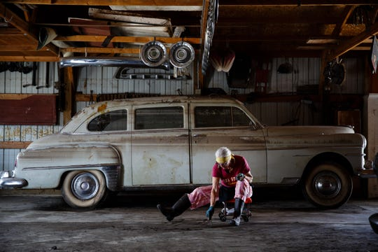 "In front of a vintage car covered in water lines, Melanie Finnell scrapes the floor of one of the buildings she owns with her husband as part of their antique business on Tuesday, April 16, 2019, in Hamburg. Finnell said they plan two sell everything and move out of Hamburg in two years. ""We've had enough floods,"" she said, ""We're not starting all over again."""