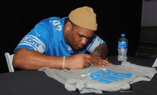 Da'Shawn Hand autographs a jersey for a fan during the Lions draft party April 25.