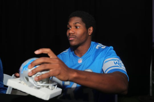 Detroit Lions running back Kerryon Johnson autographs a helmet for a fan during the draft party Thursday, April 25, 2019 at the practice facility in Allen Park.