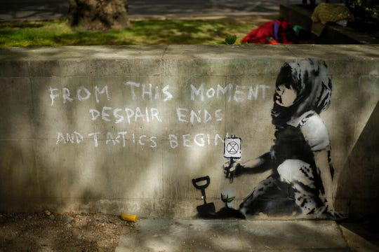 Dappled shade from a tree is cast over a new piece of street art that people noticed for the first time last night and is believed to be by street artist Banksy on a wall where Extinction Rebellion climate protesters had set up a camp in Marble Arch, London, Friday, April 26, 2019.