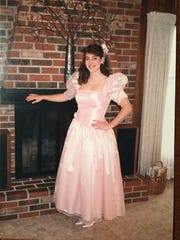Betsy Crapps poses in her pink gown before her 1988 senior prom in Rochester, New York. The pink gown is her mainstay for the annual Mom Prom in Canton — along with purple low-top Chuck Taylor sneakers.