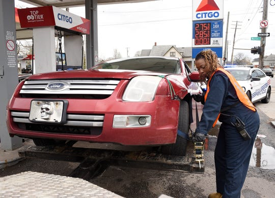 Erin Reed, a city of Detroit employee,  prepares a car for towing at a gas station on Van Dyke in Detroit on April 26. Detroit police officials credit a sharp decline in auto thefts to the city banning a company from the towing rotation and assuming most towing duties.