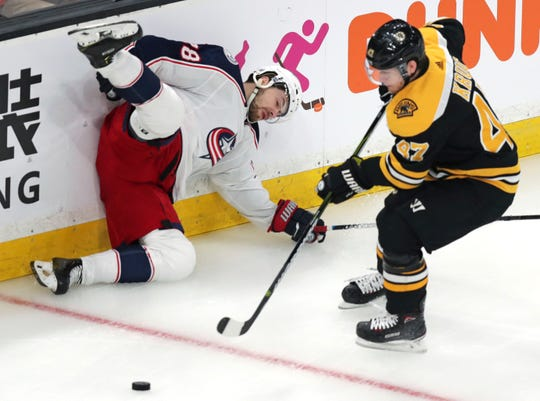 Blue Jackets right wing Oliver Bjorkstrand, left, slams into the boards after being upended by Bruins defenseman Torey Krug, right, while chasing the puck during the first period.