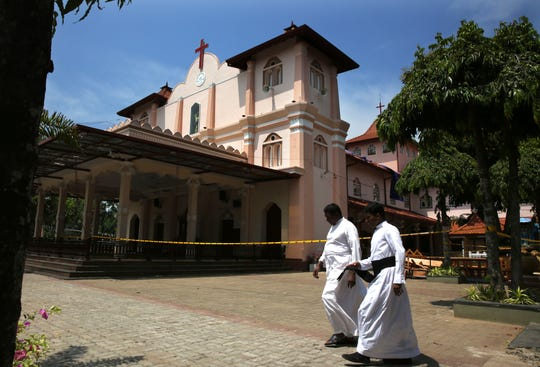 Catholic priests walk outside St. Sebastian's Church, where a suicide bomber blew himself up on Easter Sunday in Negombo, north of Colombo, Sri Lanka.