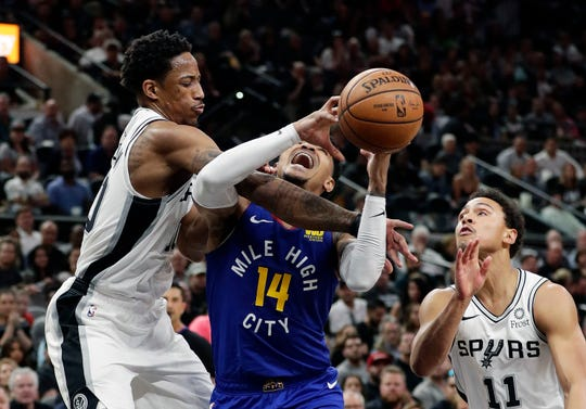 Nuggets guard Gary Harris (14) is fouled by Spurs guard DeMar DeRozan (10) during the first half.