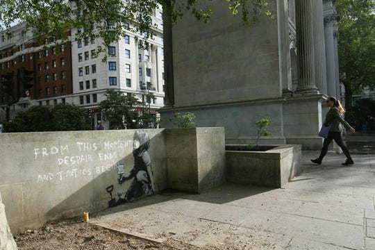 A woman walks nearby to an artwork which appears to be by street artist Banksy.