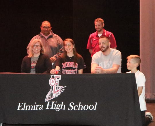 Taeli Quanz signs to run at Edinboro during a ceremony at Elmira High School on April 25, 2019.