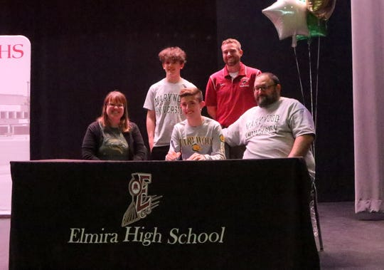 Mariano Casciotti signs to run at Marywood during a ceremony at Elmira High School on April 25, 2019.