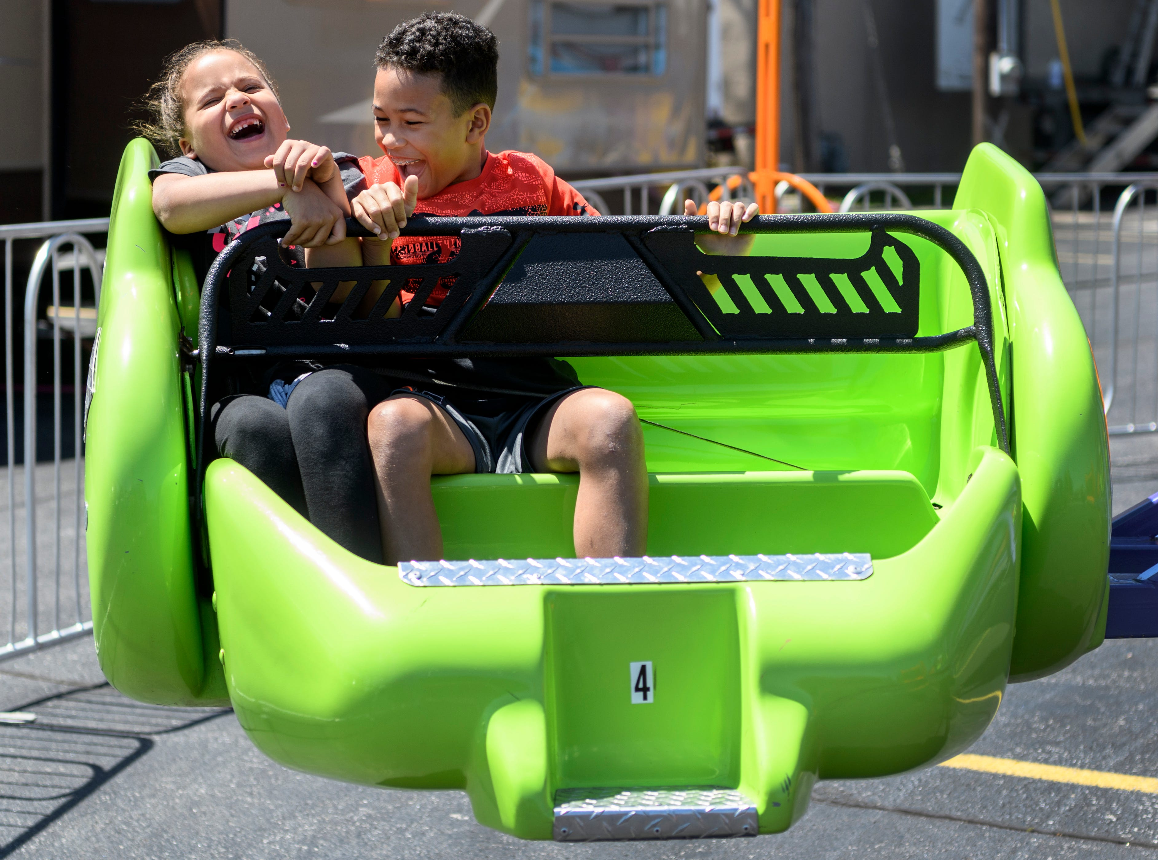 """Olivia Wilson, 6, and Dominic Sheridan, 9, both of Henderson laugh together as they ride the Sizzler during the first day of the 32nd annual Tri-Fest in downtown Henderson, Ky., Friday, April 26, 2019. """"He kept squishing me,"""" Wilson said about Sheridan, when asked if she had fun on the ride."""